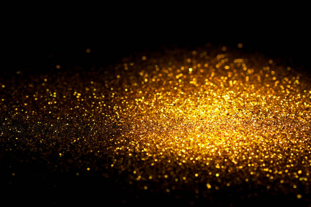 Sprinkle gold glitter dust on a black background with copy space. stock photo