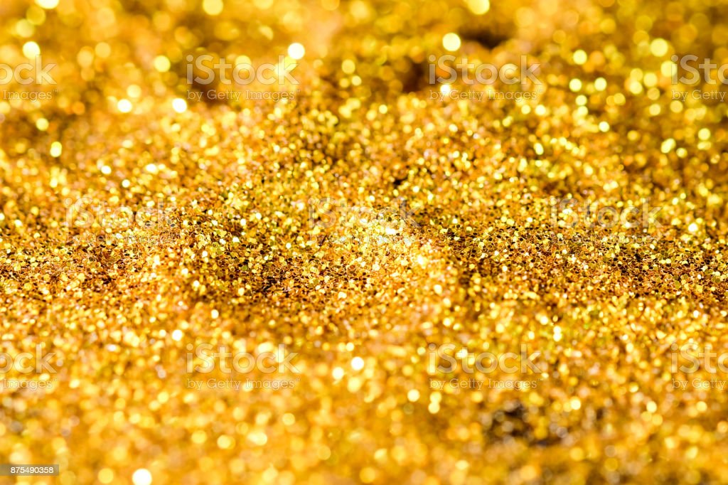 Sprinkle gold shiny dust on a black background with copy space stock photo