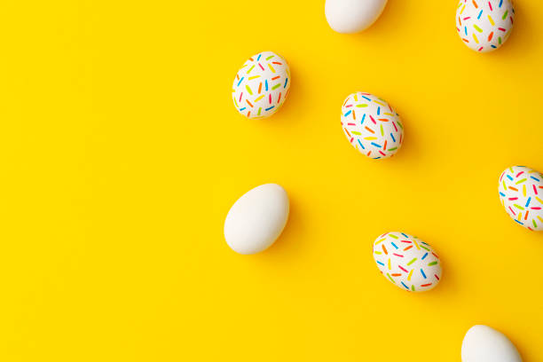 Sprinkle painted easter eggs on yellow background stock photo