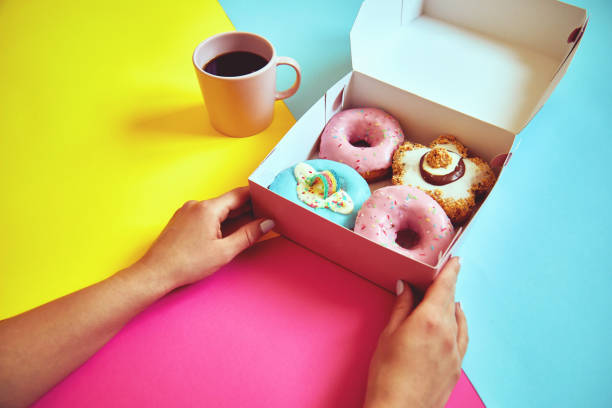 Sprinkled donuts in box and cup of coffee on colorful background. stock photo