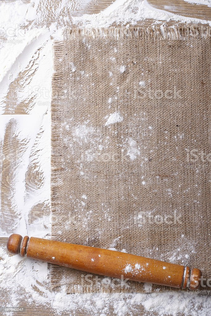 Sprinkled flour, rolling pin on a wooden board and burlap stock photo
