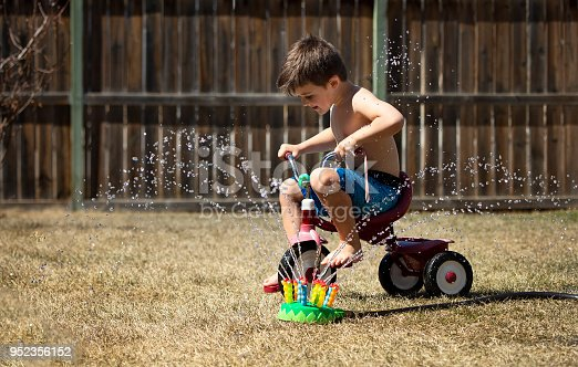 Four year old pretends he is taking his tricycle through the car wash, while driving through sprinkler spray