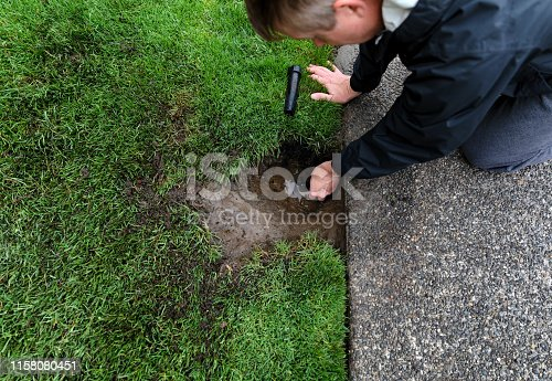 Sprinkler system being repaired by mature man with parts laying on ground
