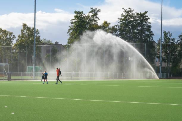 sprinklersysteem spuit een sportveld - dutch hockey stockfoto's en -beelden