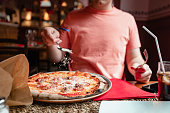 A close up motion shot of an unrecognisable person sprinkling cheese on pizza in a restaurant.