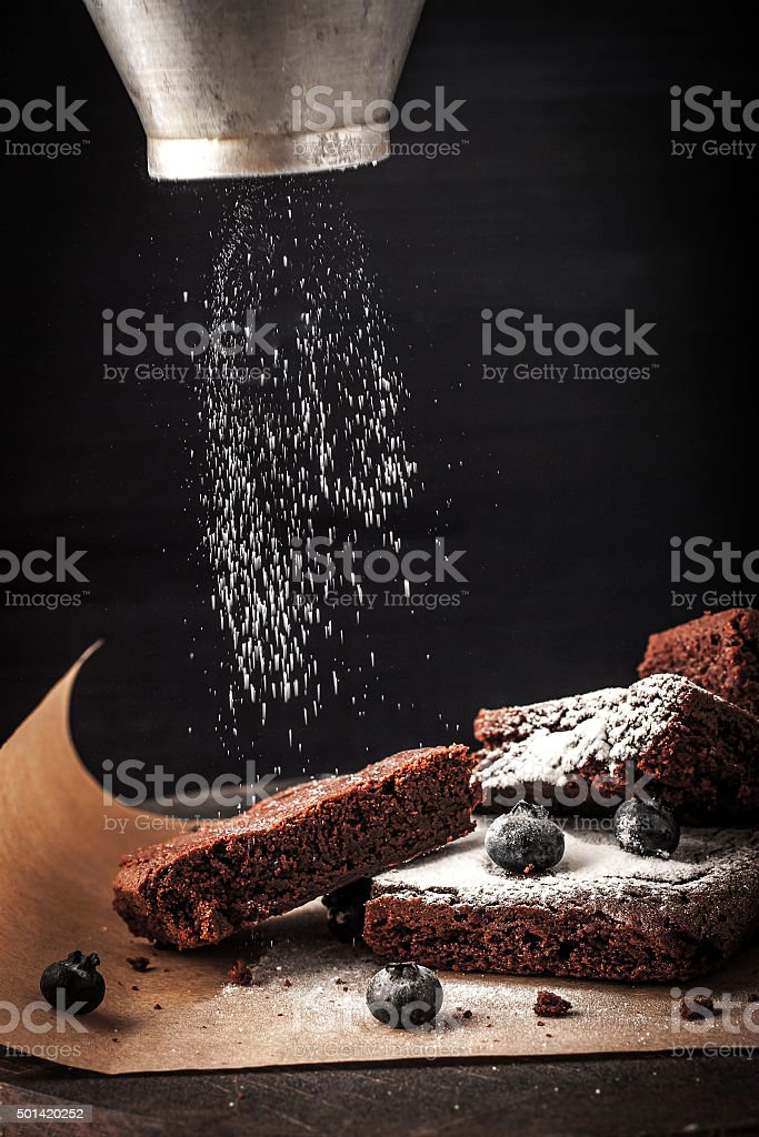 Sprinkling chocolate brownie with icing sugar and blueberry stock photo