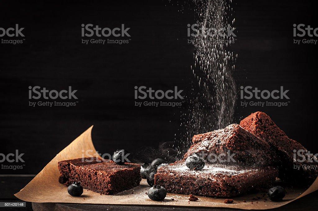 Sprinkling chocolate brownie with icing sugar horizontal stock photo