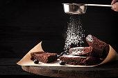 Sprinkling chocolate brownie with icing sugar