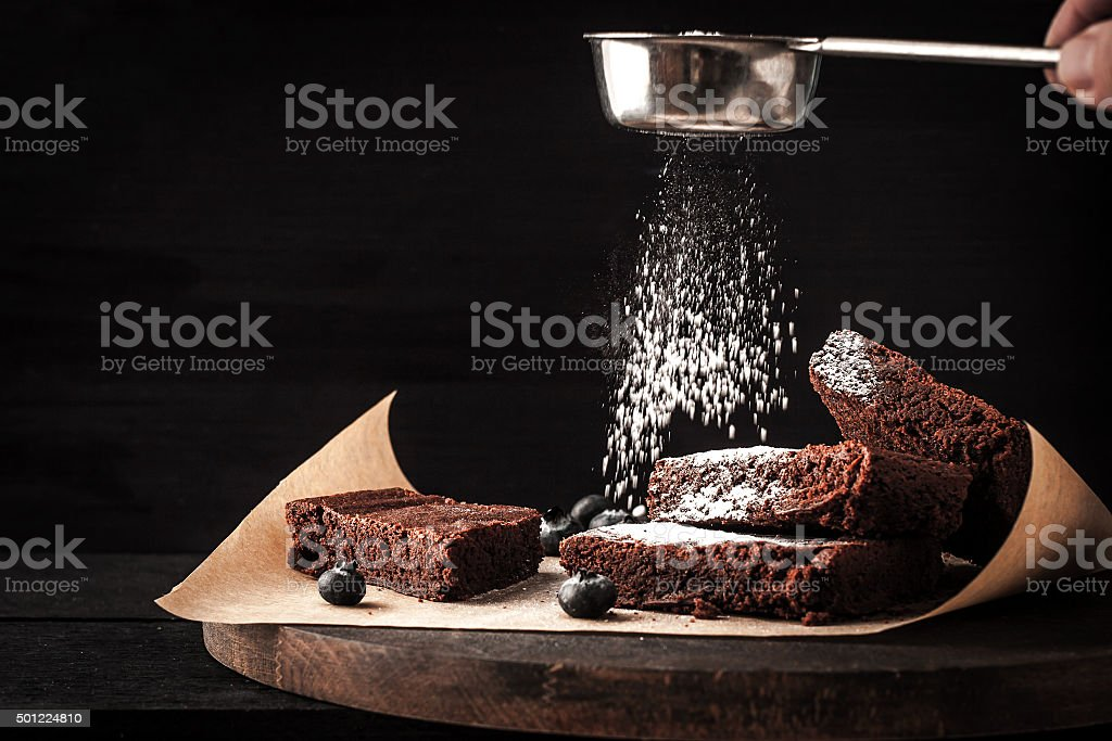 Sprinkling chocolate brownie with icing sugar stock photo