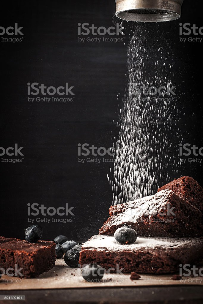 Sprinkling chocolate brownie with icing sugar vertical stock photo
