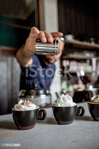 Unrecognizable male sprinkling cinnamon on top of whipped cream in mocha coffee at the industrial coffee shop.