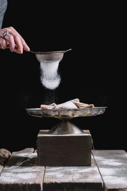 sprinkling cookies with powdered sugar - food styling stock photos and pictures