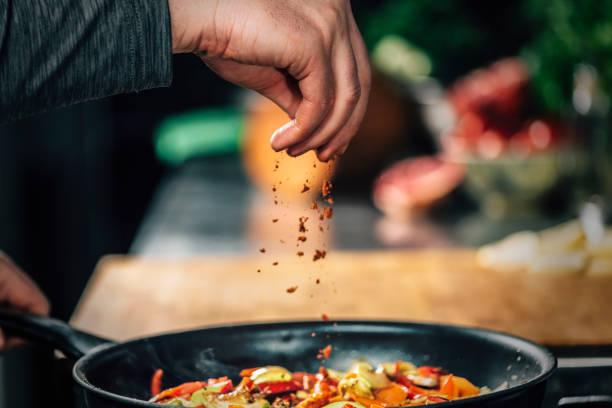polvilhe moída red chili pepper páprica sobre legumes fatiados - condimento temperos - fotografias e filmes do acervo