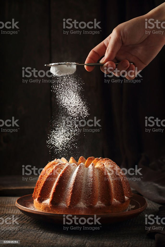 Sprinkling of orange cake with powdered sugar stock photo