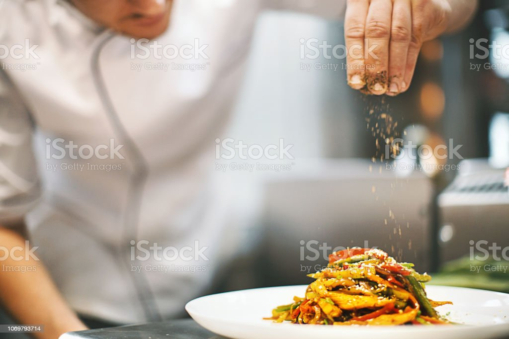 Sprinkling seasonings from high up. - Foto stock royalty-free di Abilità