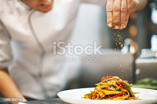 Unrecognizable male chef sprinkling spices on a dish in a commercial kitchen.