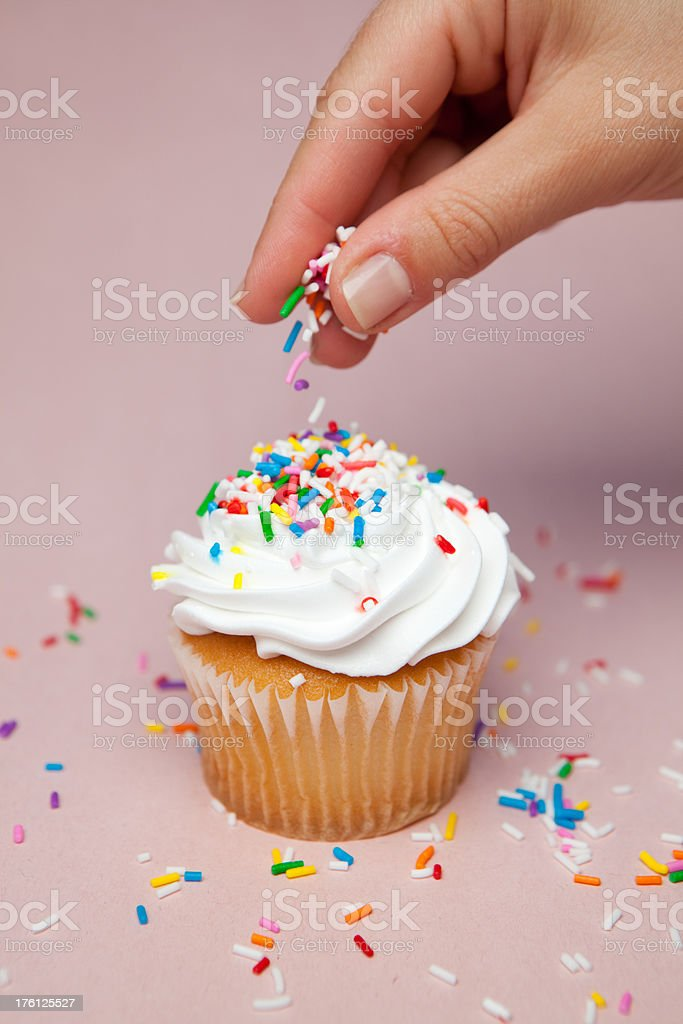 sprinkling sprinkles on cupcake stock photo