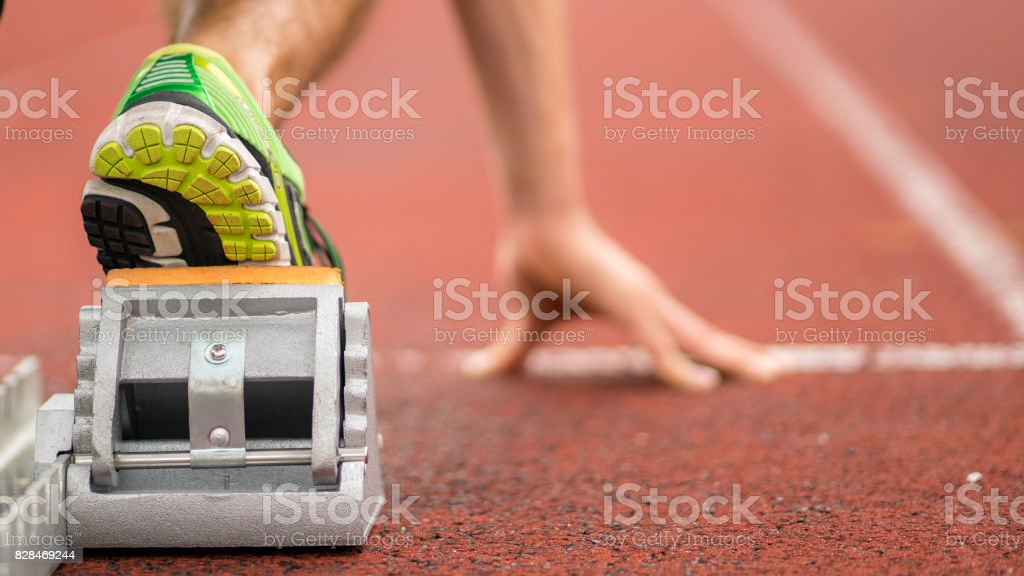 sprint start in track and field detail of hand and feet in sprint start in track and field All-Weather Running Track Stock Photo