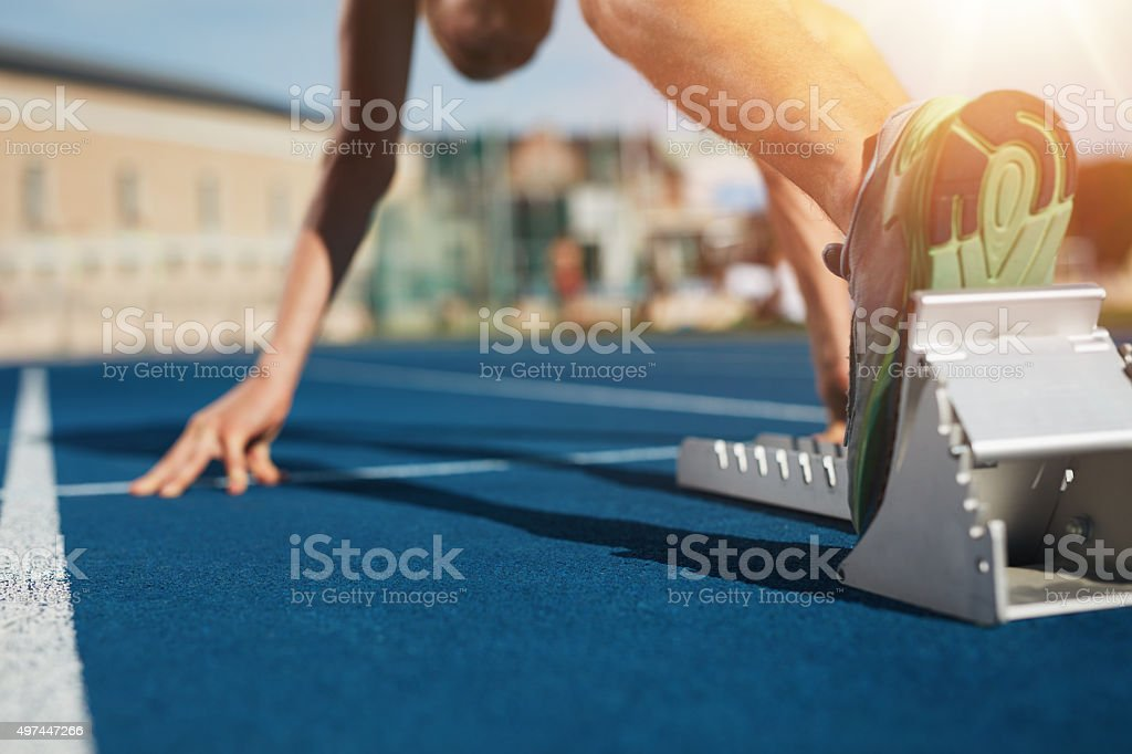 Sprint start on race track Feet on starting block ready for a spring start.  Focus on leg of a athlete about to start a race in stadium with sun flare. 2015 Stock Photo