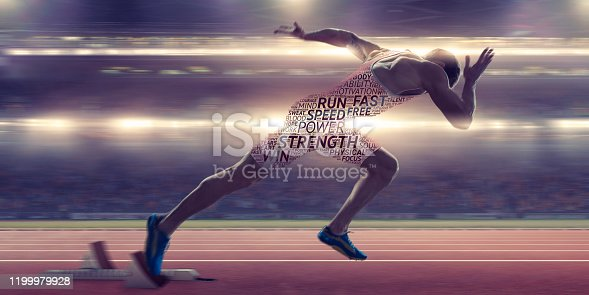 A conceptual image of a male athlete sprinting out from the starting blocks on a running track in a floodlit stadium. His body is covered with a motivational word cloud with positive words in differing fonts and sizes. With motion blur.