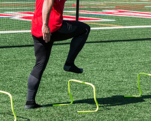 Sprinter doing running drills over mini hurdles stock photo