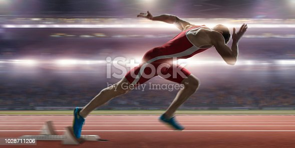 Close up image of a professional male sprinter in mid action warm up, having just burst out of the blocks on an athletics track. The athlete is wearing a red and white body suit and spikes. The action occurs in a generic floodlit stadium full of spectators during a night time competition.