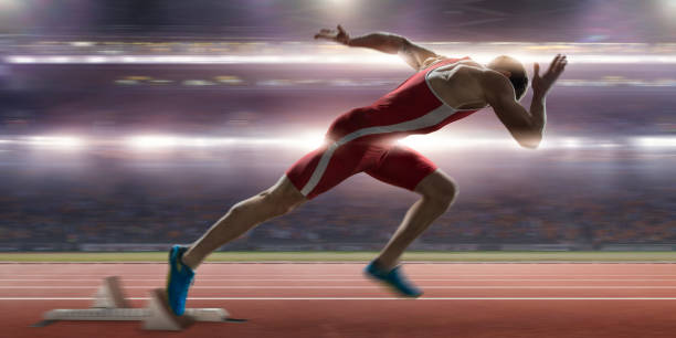 Sprinter High Speed Burst From Blocks At Stadium Athletics Event Close up image of a professional male sprinter in mid action warm up, having just burst out of the blocks on an athletics track. The athlete is wearing a red and white body suit and spikes. The action occurs in a generic floodlit stadium full of spectators during a night time competition. sprint stock pictures, royalty-free photos & images