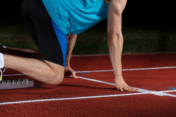 sprinter leaving starting blocks on the running track in front of big modern stadium with lights. explosive start. - carpet runner stock photos and pictures