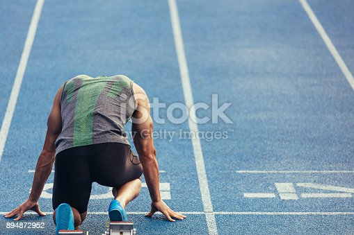 istock Sprinter on his marks on a running track 894872952