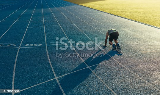 istock Sprinter on his marks on a running track 907855888
