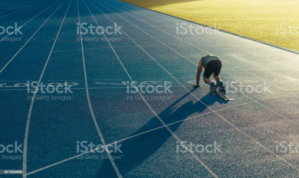 Sprinter on his marks on a running track stock photo