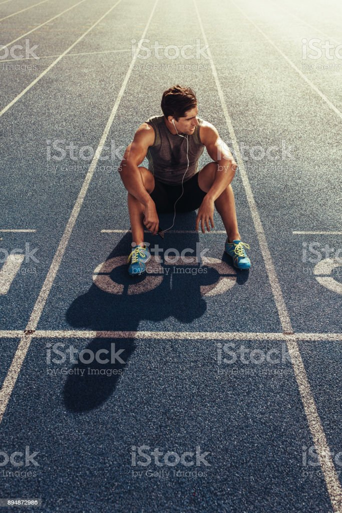 Sprinter relaxing on running track stock photo