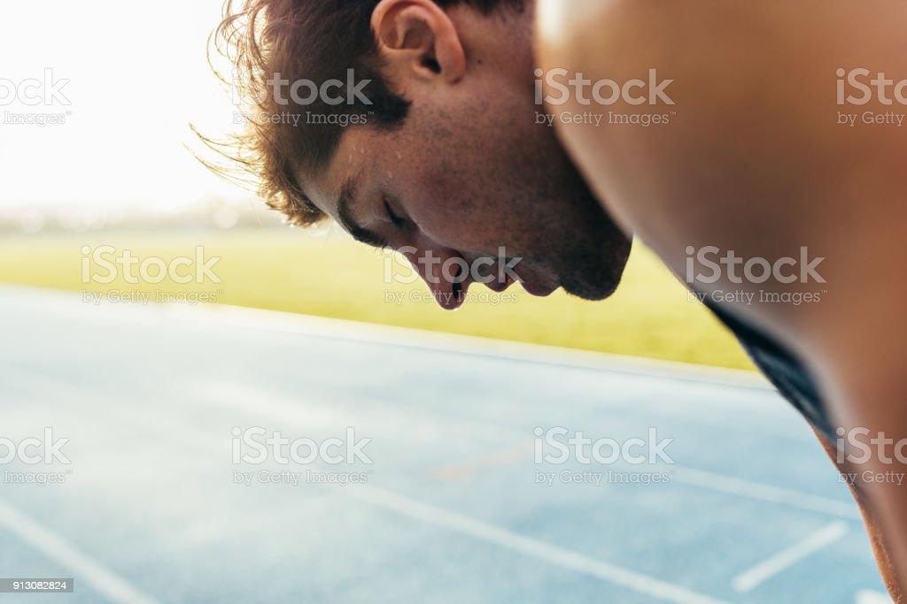Sprinter standing on running track stock photo