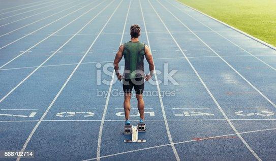 istock Sprinter standing on starting block on running track 866702714