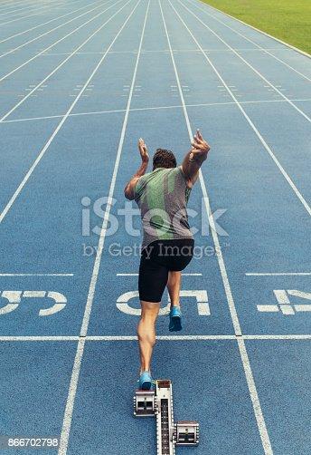 istock Sprinter taking off from starting block on running track 866702798