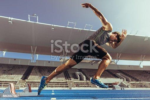istock Sprinter taking off from starting block on running track 880562262