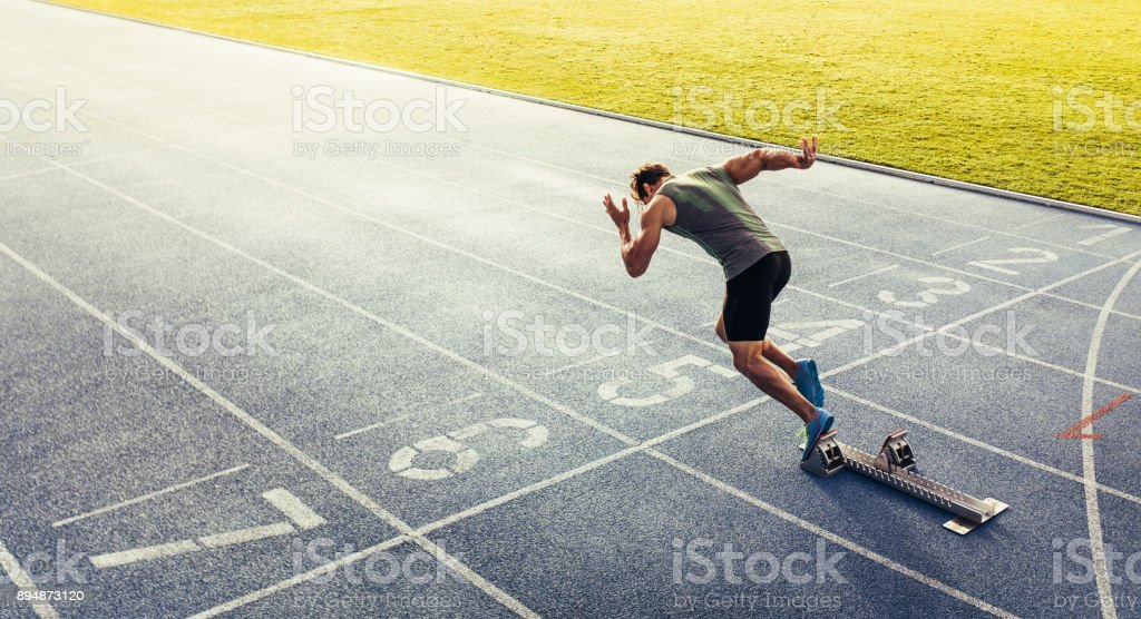 Sprinter taking off from starting block on running track Rear view of an athlete starting his sprint on an all-weather running track. Runner using starting block to start his run on race track. Active Lifestyle Stock Photo