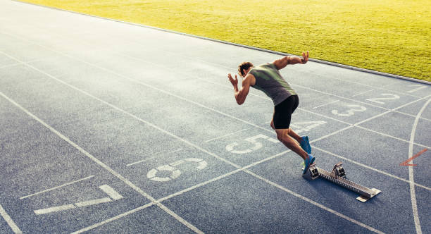 Sprinter taking off from starting block on running track Rear view of an athlete starting his sprint on an all-weather running track. Runner using starting block to start his run on race track. sprint stock pictures, royalty-free photos & images