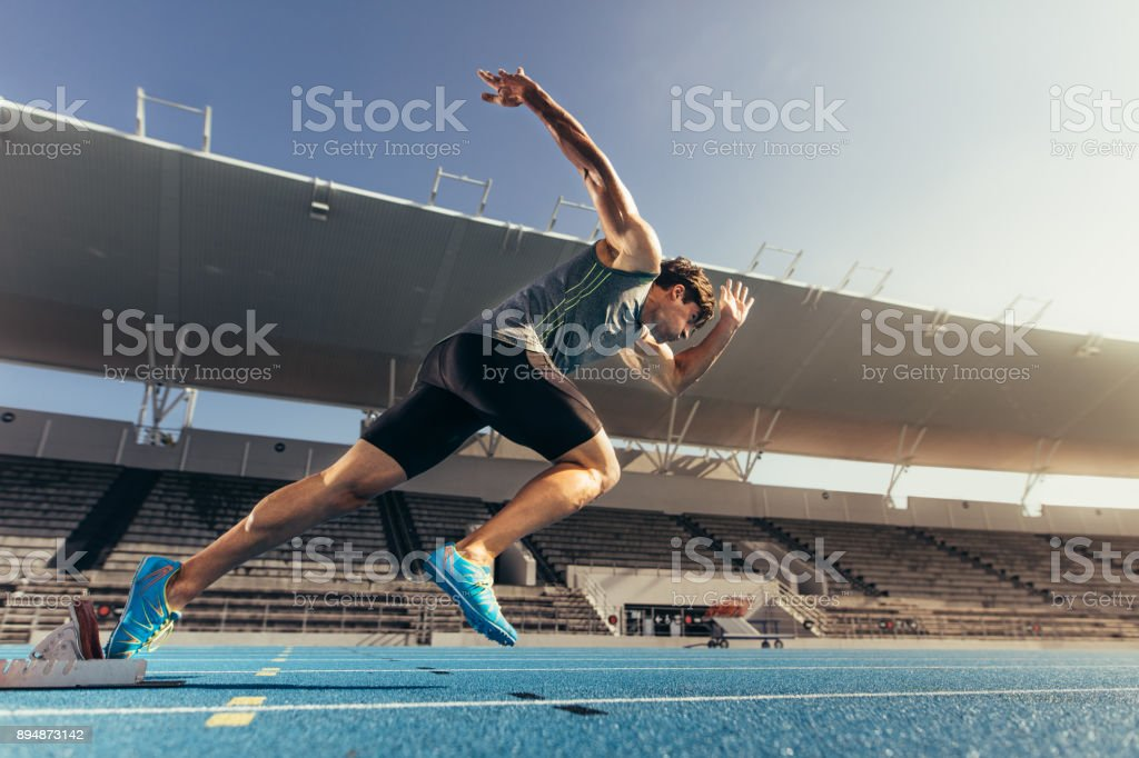 Sprinter taking off from starting block on running track stock photo