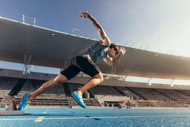 sprinter taking off from starting block on running track - athlete stock photos and pictures