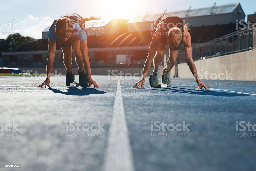 Sprinters at starting blocks ready for race Sprinters at starting blocks ready for race . Athletes at starting position on athletics stadium race track with sun flare. 2015 Stock Photo
