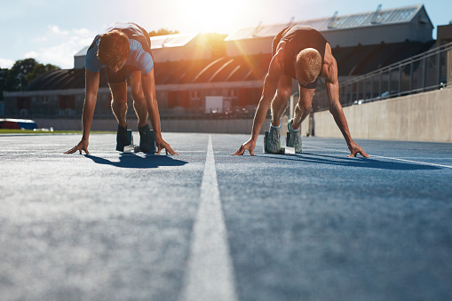 Sprinters At Starting Blocks Ready For Race Stock Photo - Download Image Now