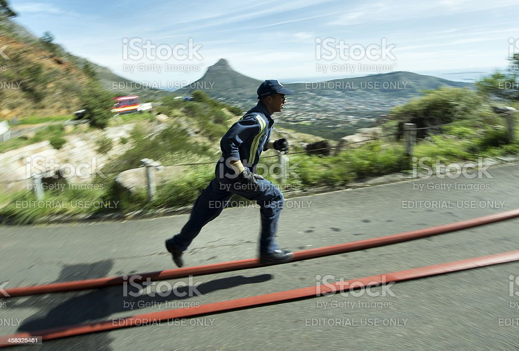 Sprinting firefighter against Table Mountain slope royalty-free stock photo
