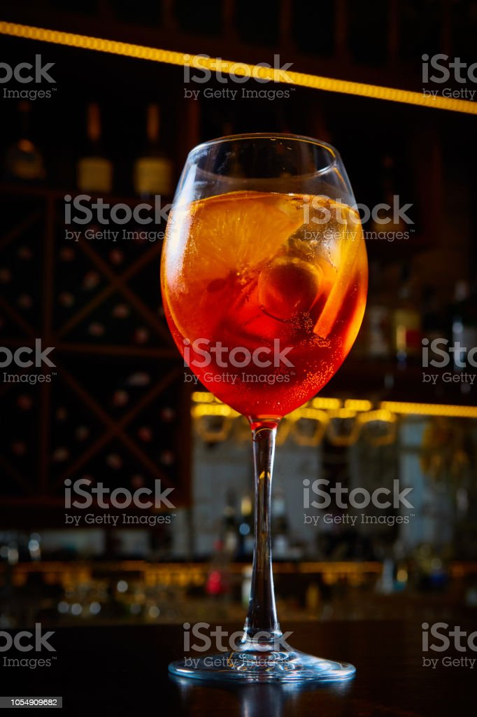 Aperol Spritz Cocktail Alcoholic beverage based on bar counter with ice cubes and oranges stock photo