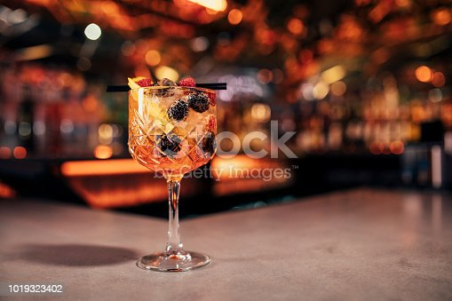 Front view of a Aperol Spritz cocktail on a bar counter. The background of the image is defocused lights and the back of the bar. This cocktail has blackberries and raspberries as a garnish on the cold drink.