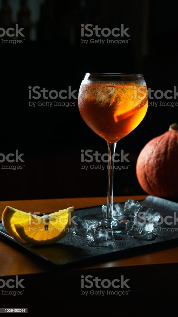 Aperol Spritz cocktail with pumpkin and orange slices and ice on black tray on dark for celebration. Halloween and autumn concept stock photo