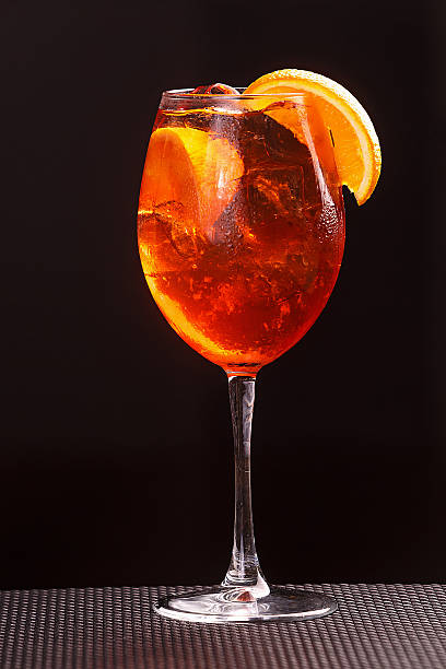aperol spritz in glass, close up on black background - sprizz stock-fotos und bilder