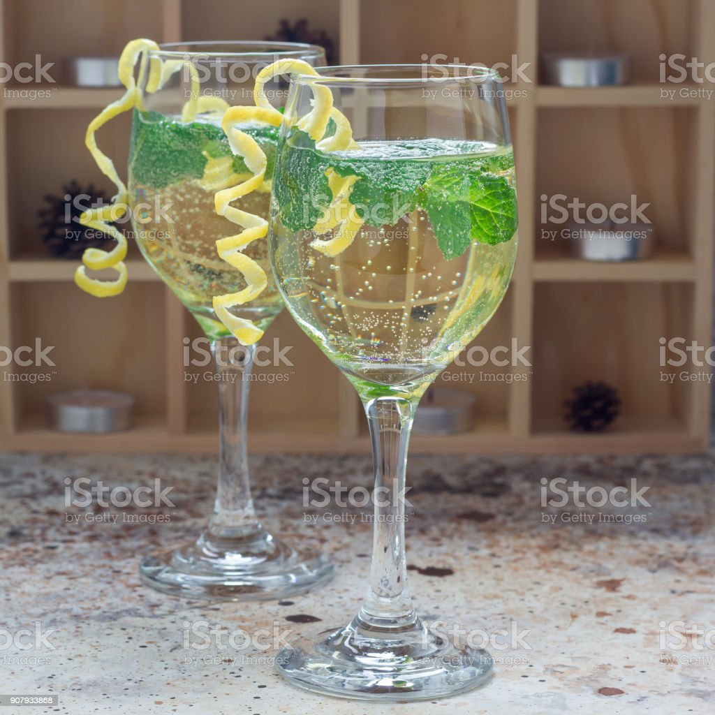 Spritzer cocktail with white wine, mint and ice, decorated with spiral lemon zest, square stock photo