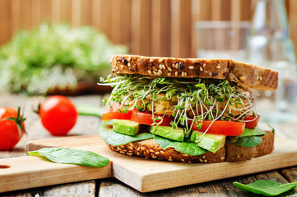 sprouts avocado tomato spinach chickpeas burger rye sandwich - sandwich stock pictures, royalty-free photos & images