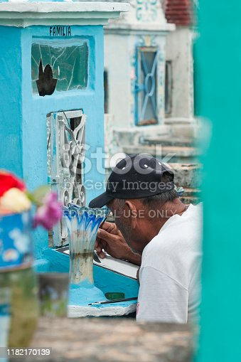 Yucatan, Mexico - October 30, 2008: An adult Hispanic man wearing a black baseball hat and white tshirt paints the blue colored headstone as is the annual tradition to spruce up family plots at the cemeteries during Days of the Dead.